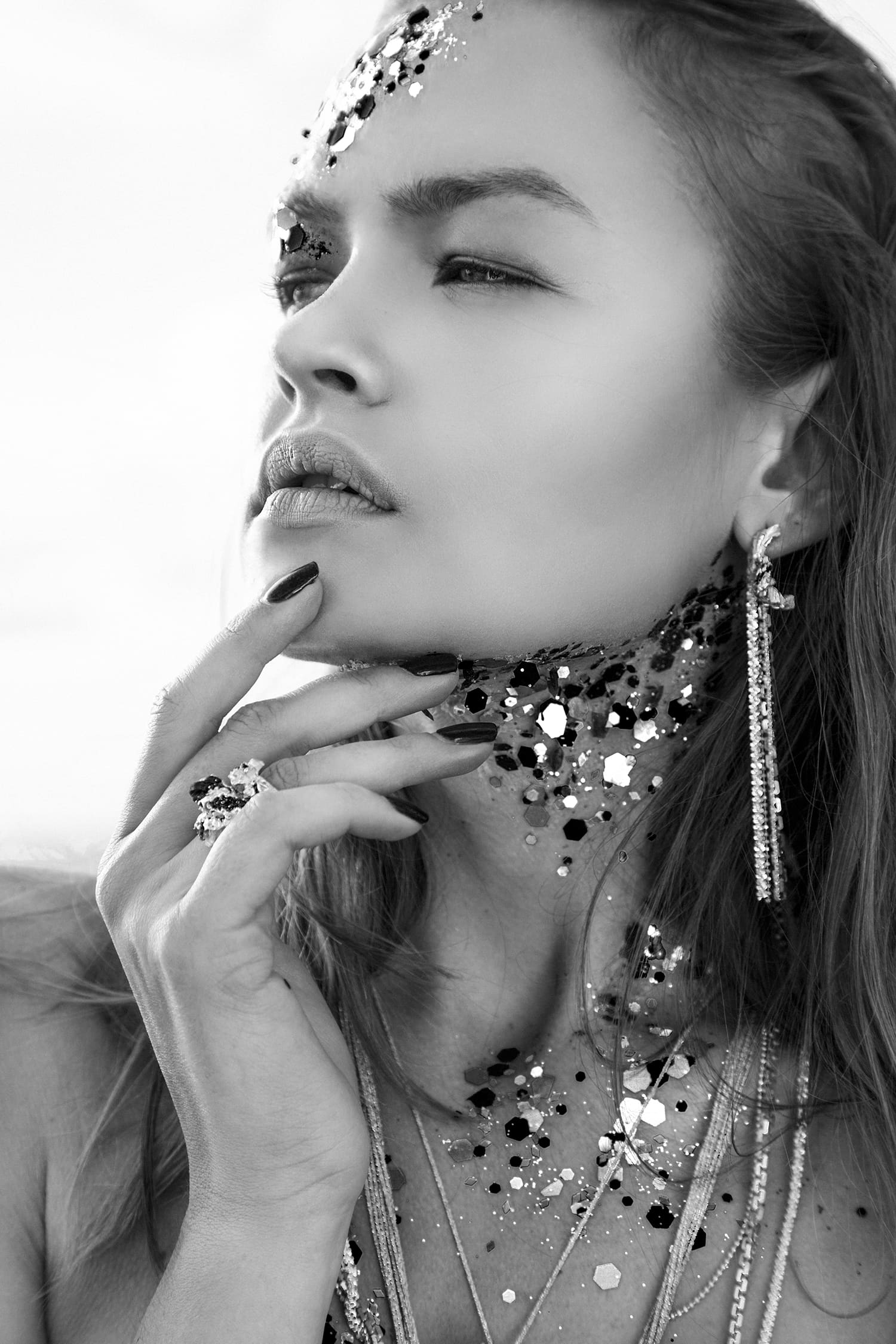Black and white image of model wearing contemporary Anomaly jewelry.