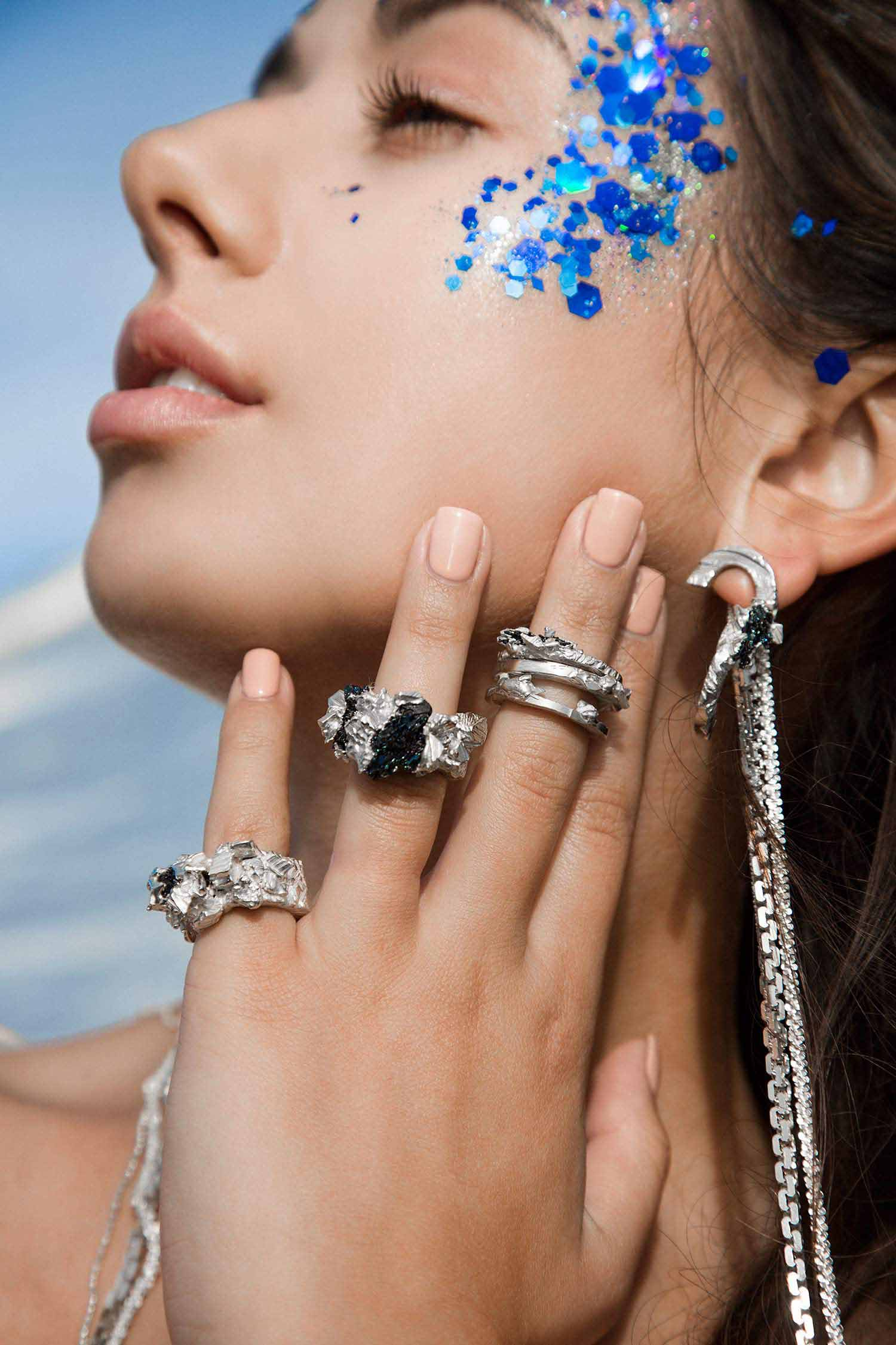 Close-up image of model in the sea, wearing Zydrune statement rings and long chain fashion earrings.