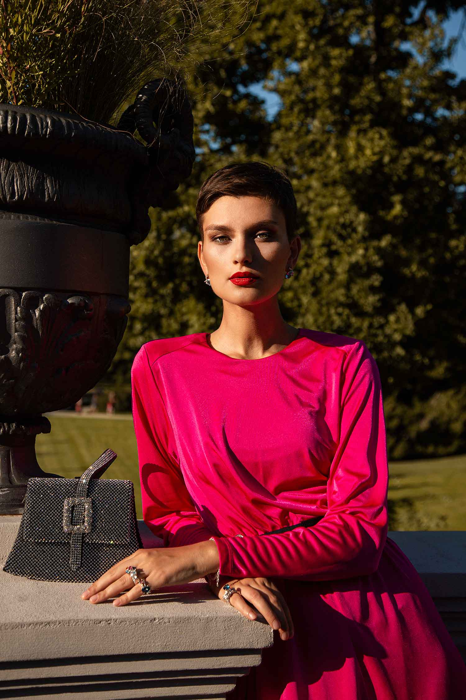 Model outdoors in pink vintage dress, wearing red lipstick and Zydrune statement jewellery.