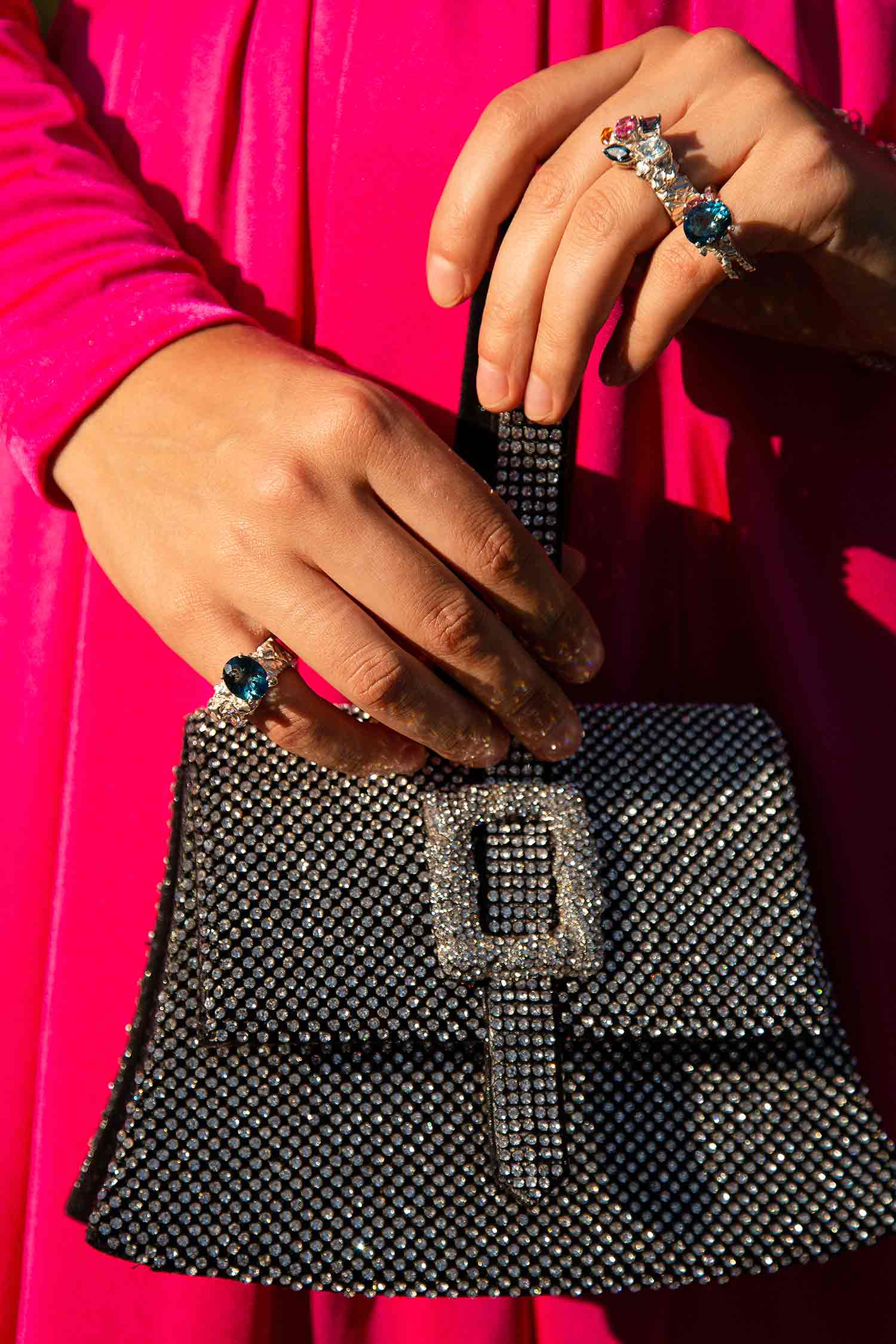 Close-up of model hands holding shiny purse and wearing Zydrune Celestial colourful gemstone rings.
