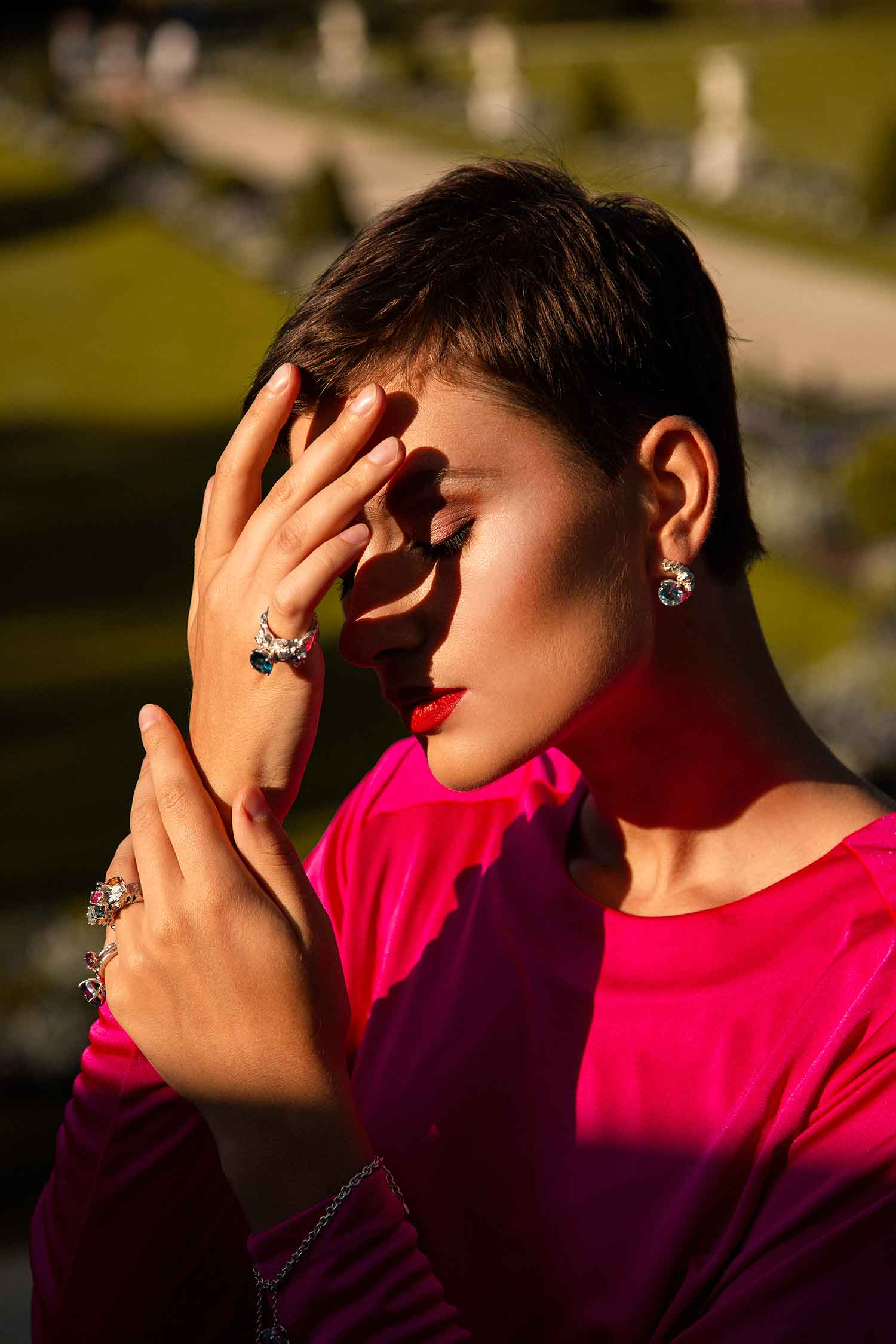 Close-up of model outdoors wearing Zydrune multi gemstone rings and Topaz earrings.