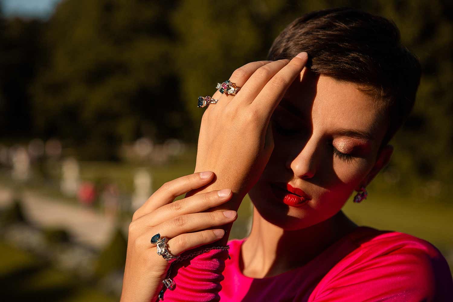 Model covering her face from the sun with her hand and wearing Zydrune handmade jewelry.