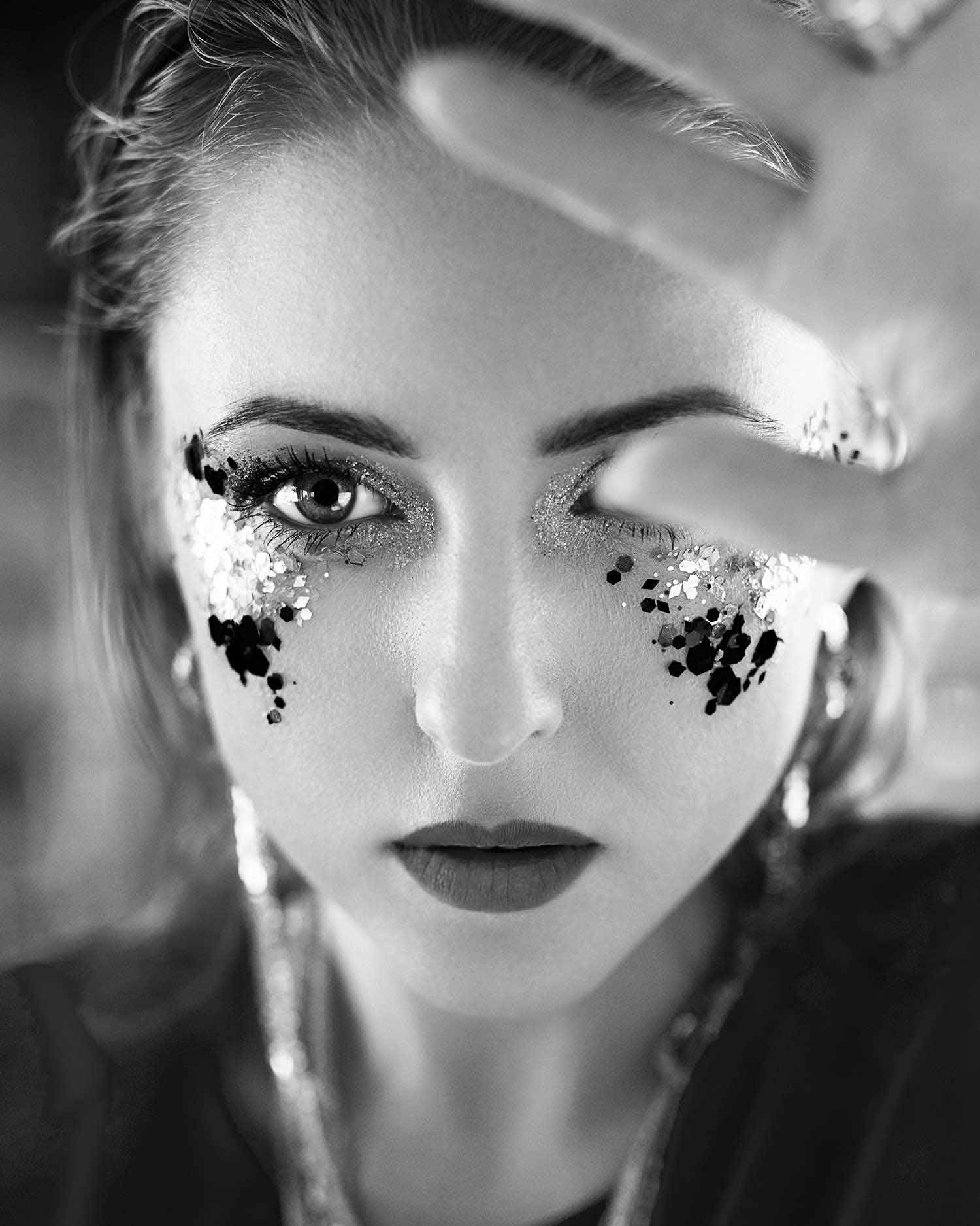 Black and white image of model with glitter makeup, wearing Zydrune Anomaly earrings.