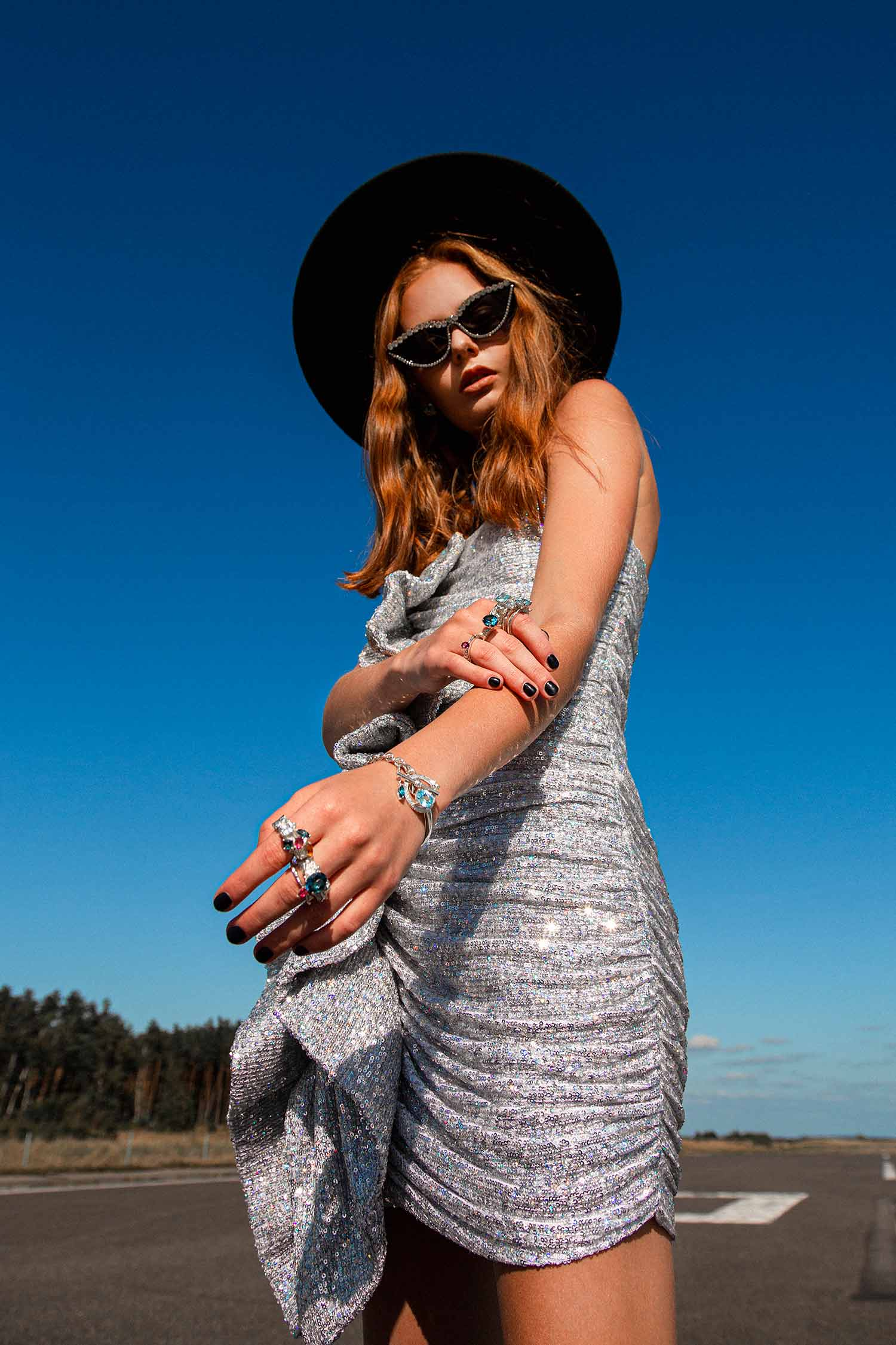 Model on the road, wearing shiny dress, cowboy hat, sunglasses and Zydrune high-end jewellery.