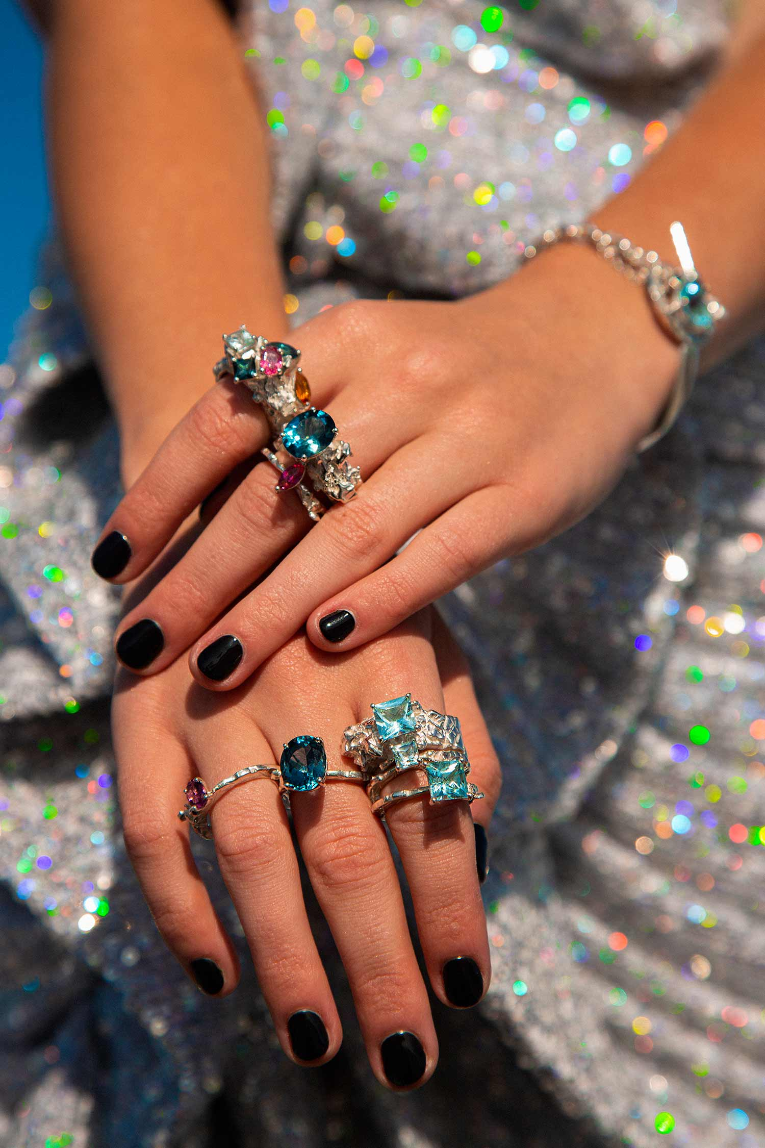 Close-up of model hands fully covered in Zydrune handmade gemstone rings.