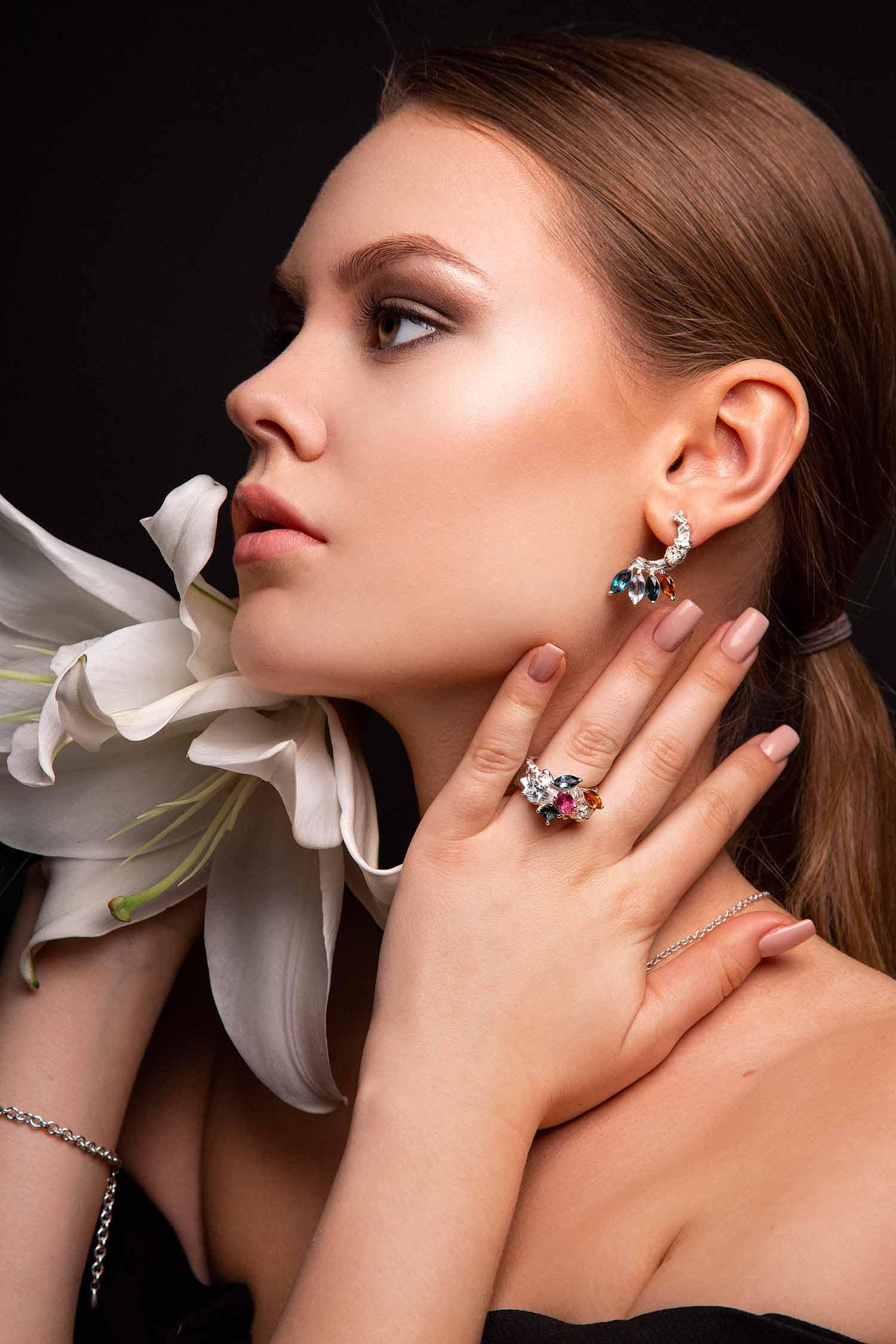 Portrait of model with lilies wearing Zydrune statement ring and earrings.