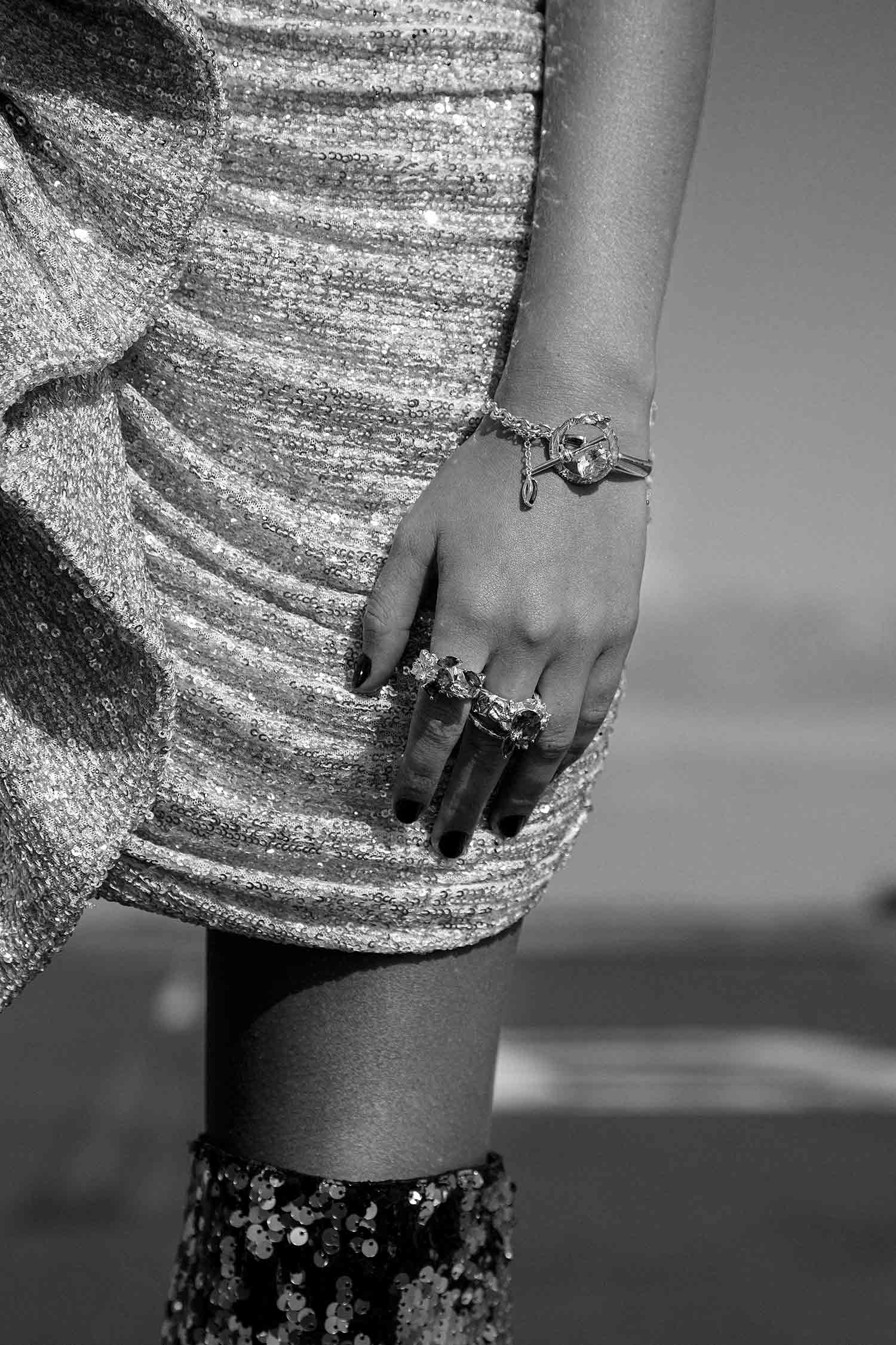 Black and white close-up image of model with Zydrune gemstone bracelet and statement big rings.