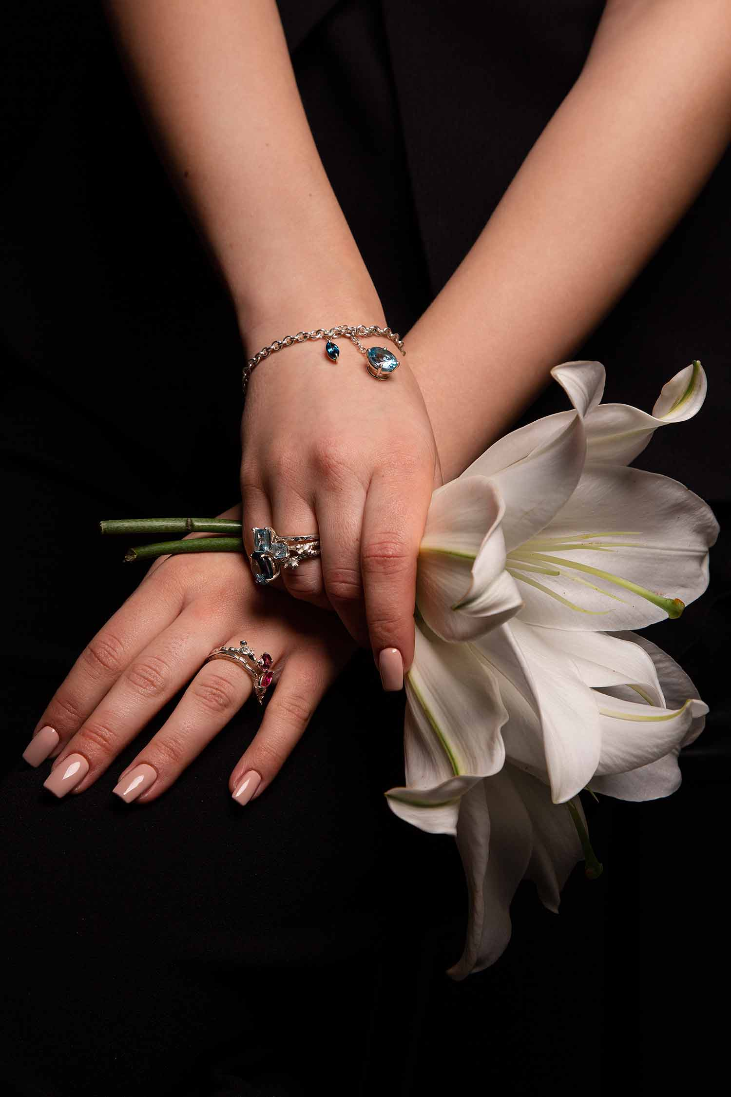 Close-up of model hands holding lilies and wearing Zydrune stacking rings and Topaz bracelet.