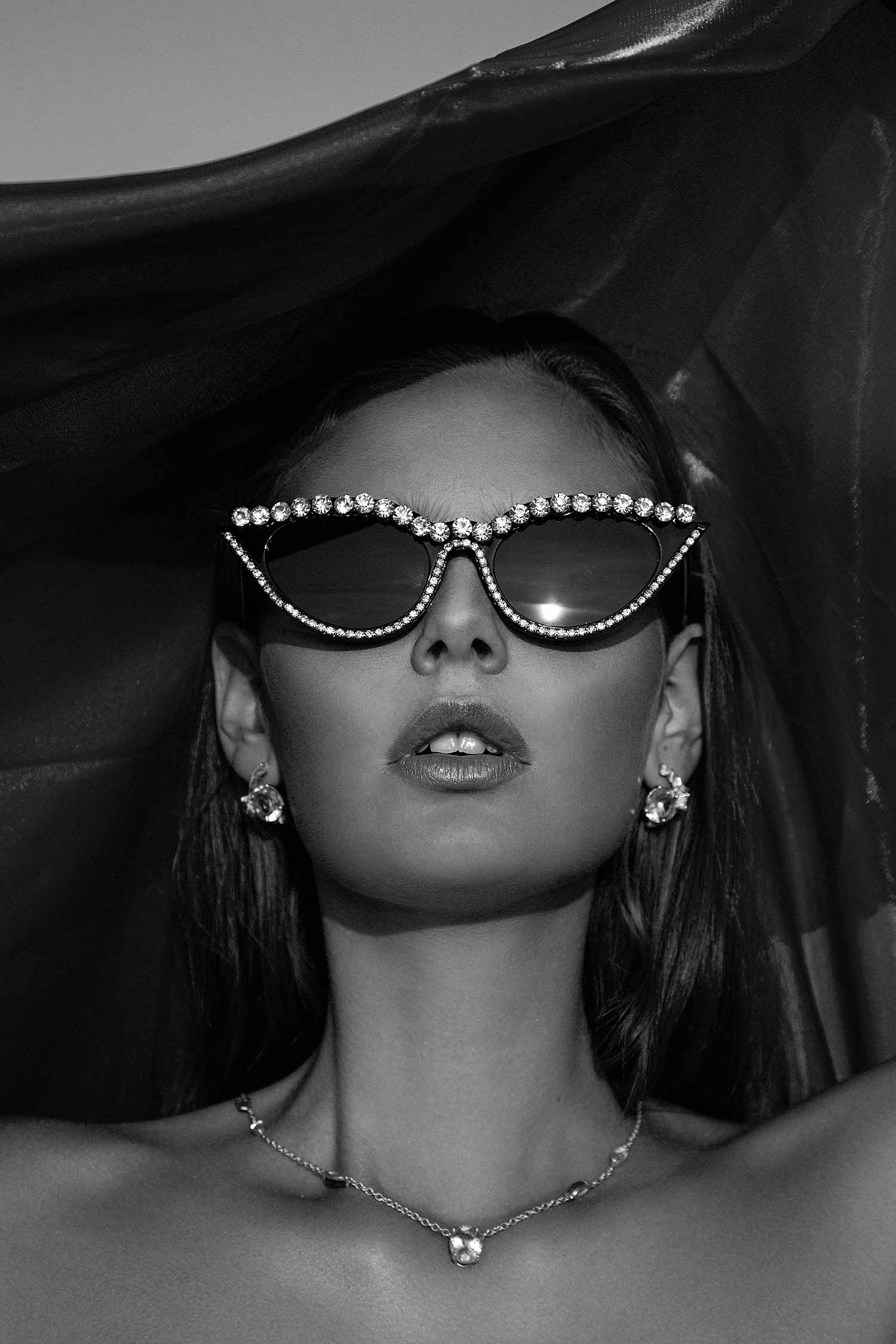 Black and white image of model with Zydrune statement jewellery and black diamante sunglasses.