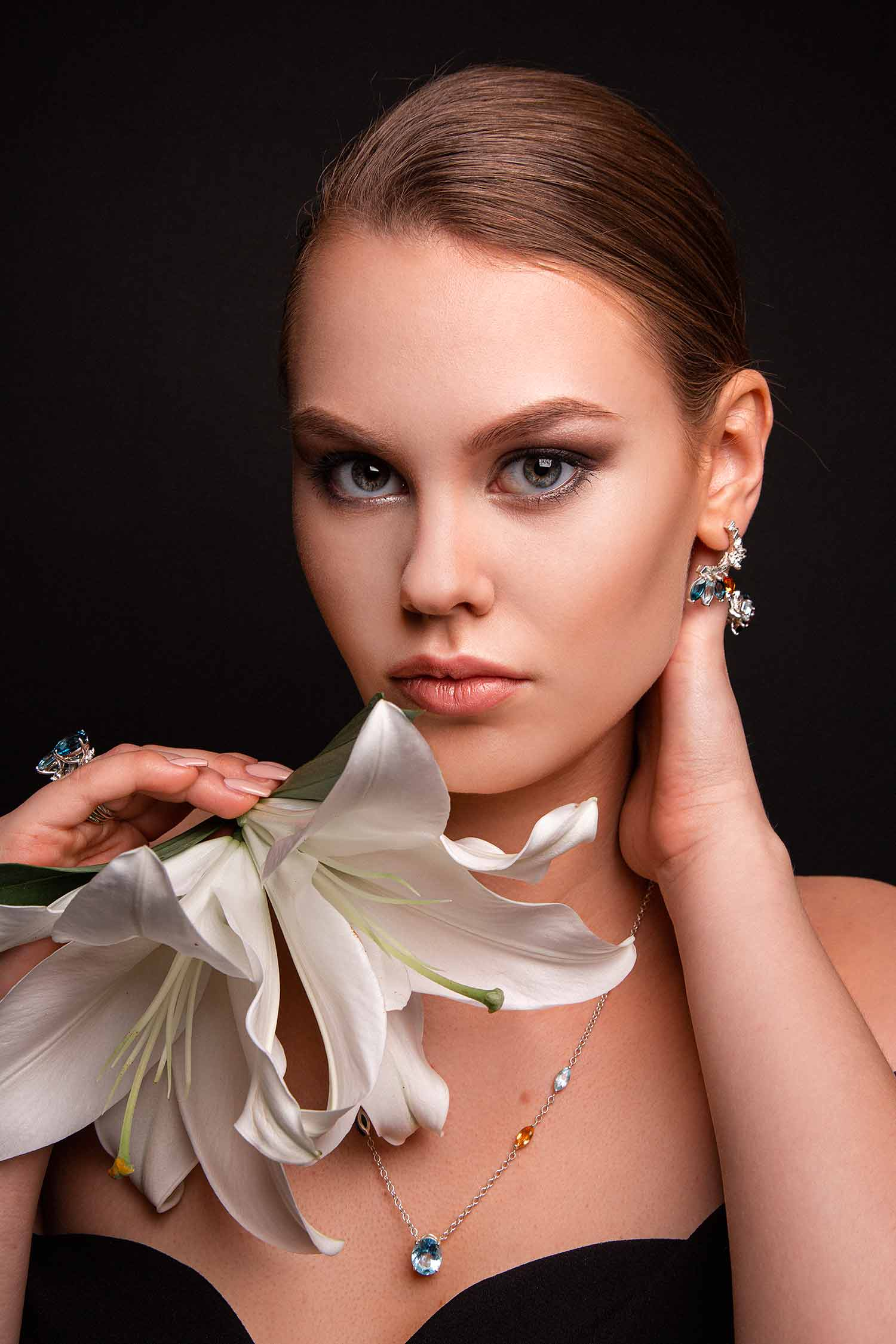 Model with lilies wearing Zydrune ethically made gemstone jewellery.