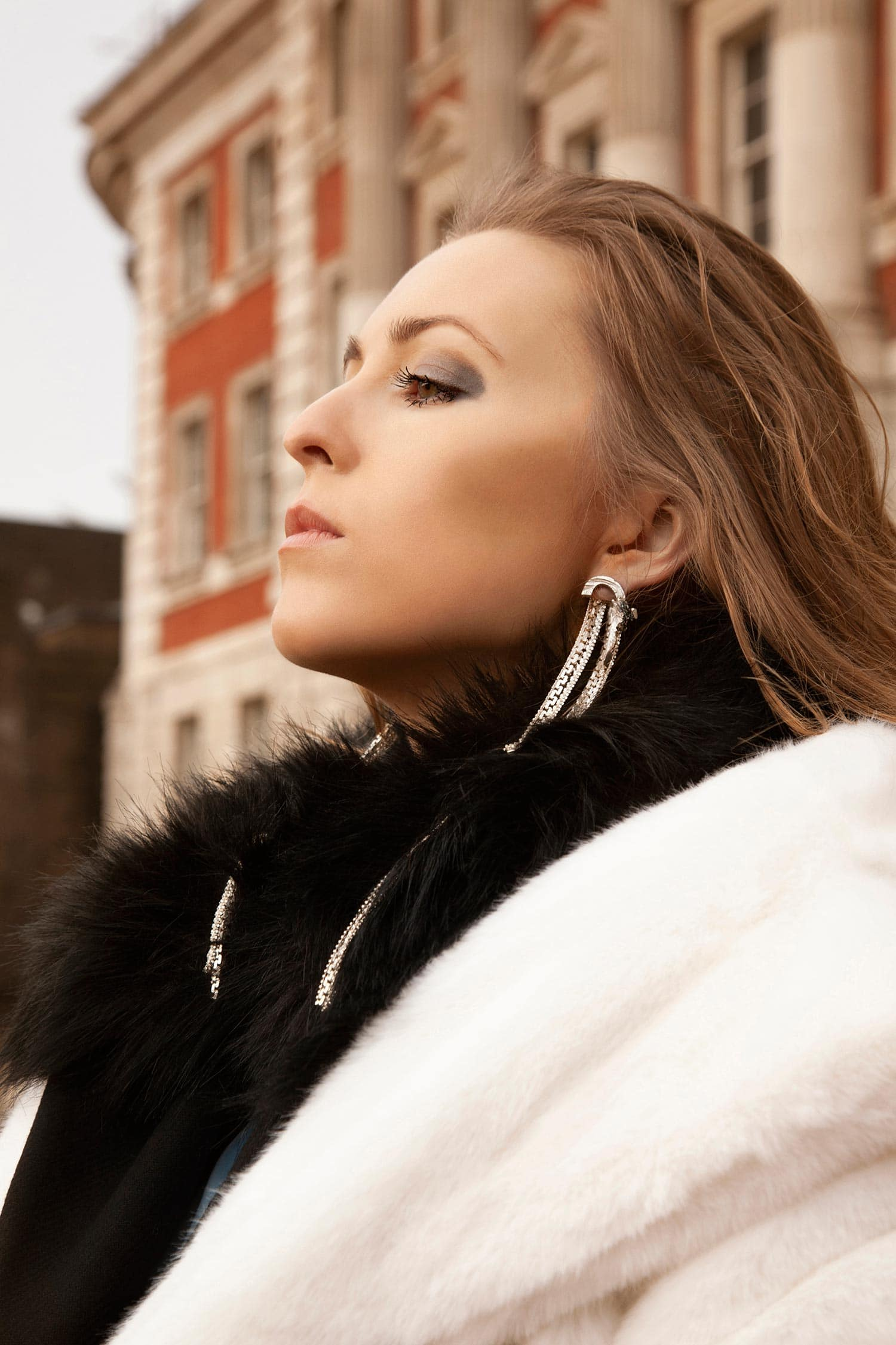 Zydrune high-end jewellery lookbook. Model wearing white and black fur coat and statement earrings.