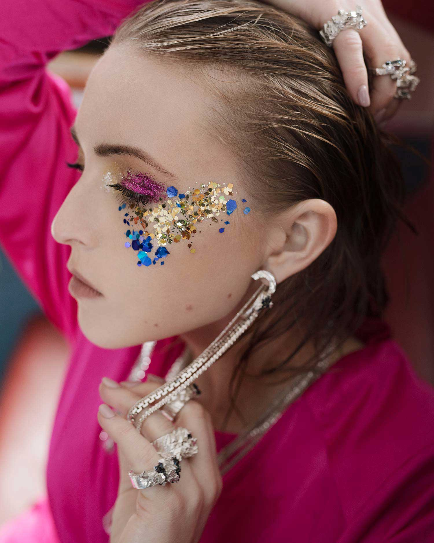 Portrait of model with glitter makeup wearing Zydrune Anomaly earrings and one-off rings.