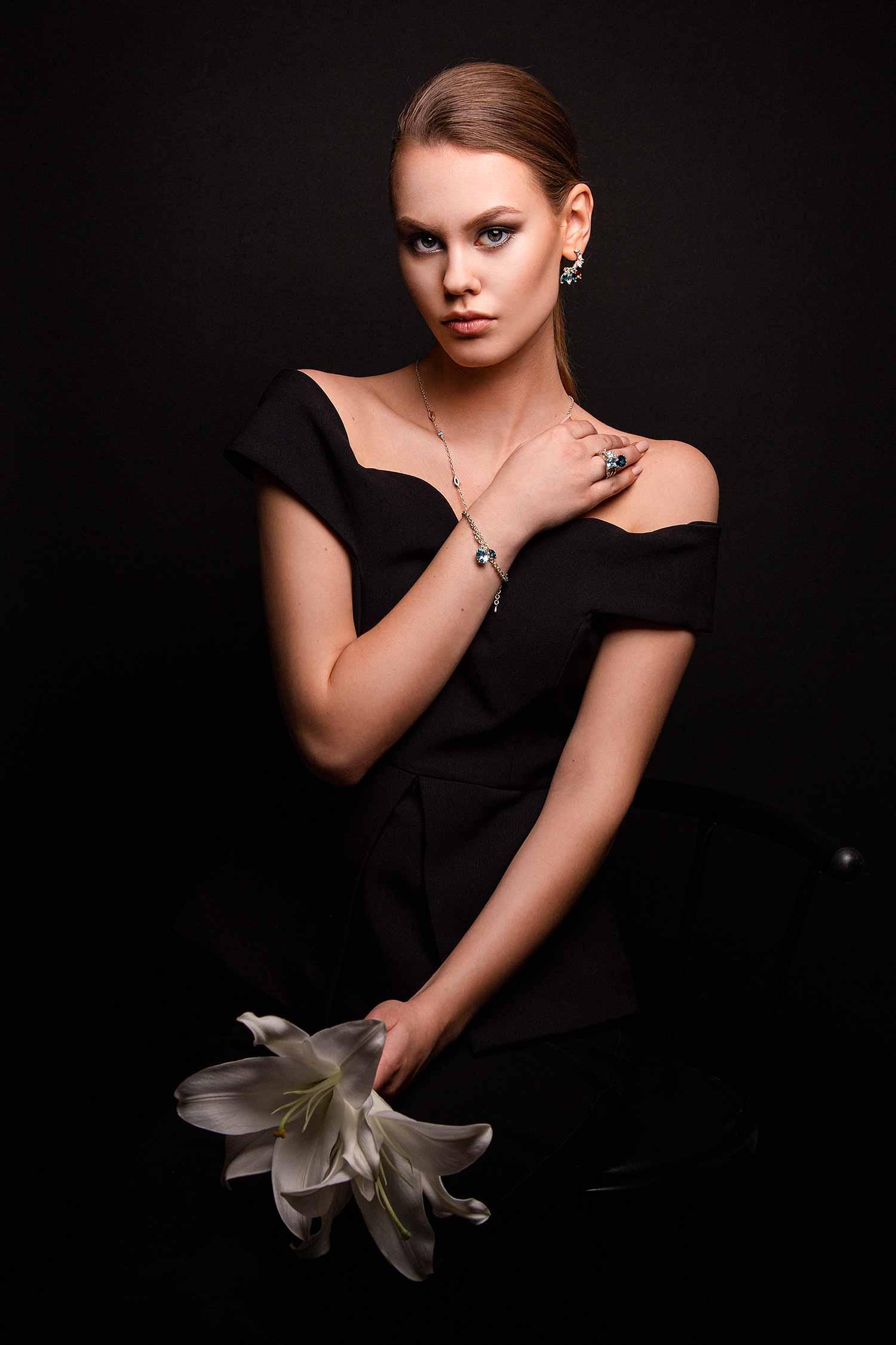 Model dressed in black elegant dress, holding lilies and wearing Zydrune gemstone jewelry.