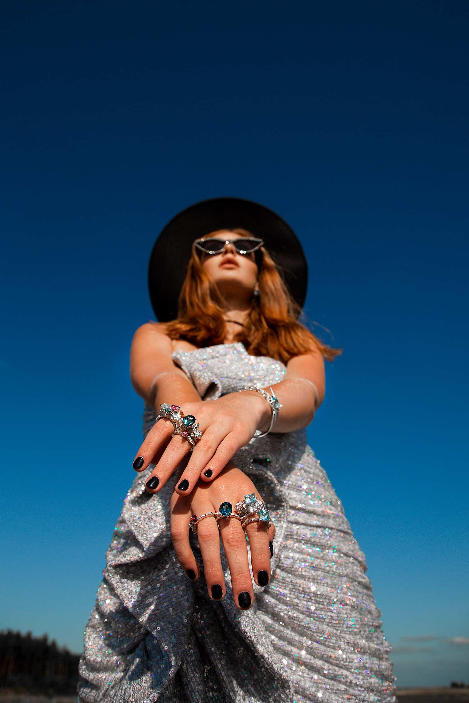 Model wearing cowboy hat, sunglasses, shiny dress and Zydrune gemstone rings and bracelet.