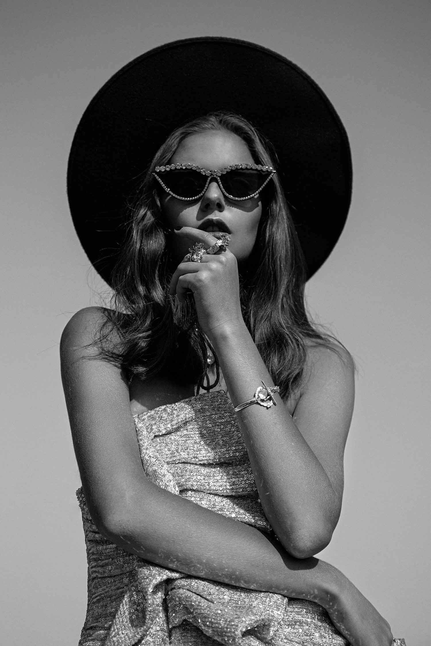 Black and white image of fashion model with Zydrune high-end gemstone bracelet and statement rings.