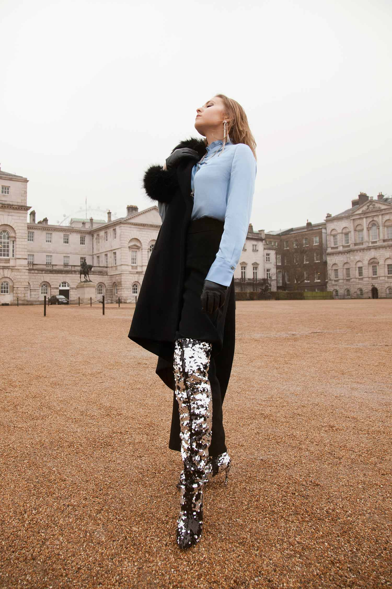 Model in shiny over the knee boots, elegant black trousers, silky blue blouse and Zydrune jewelry.