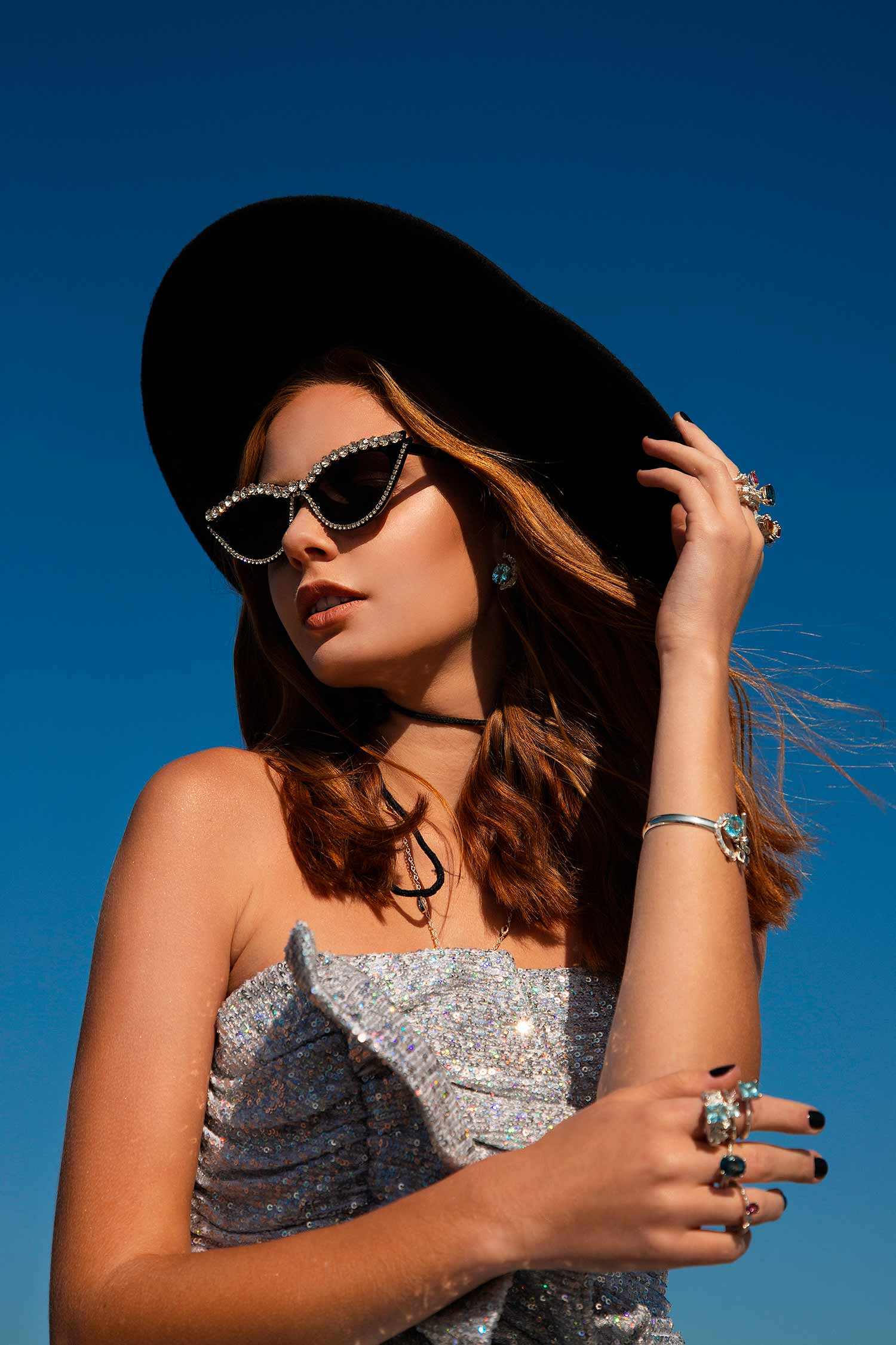 Close-up of model in shiny dress, black sunglasses and a hat wearing Zydrune designer jewellery.
