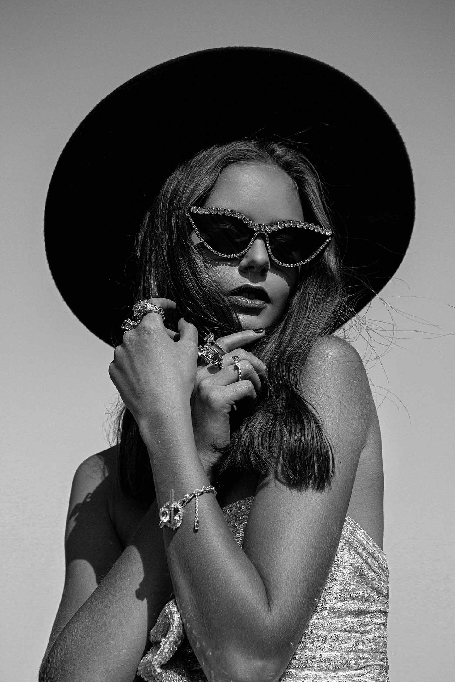 Black and white image of fashion model with Zydrune gemstone bracelet and statement big rings.