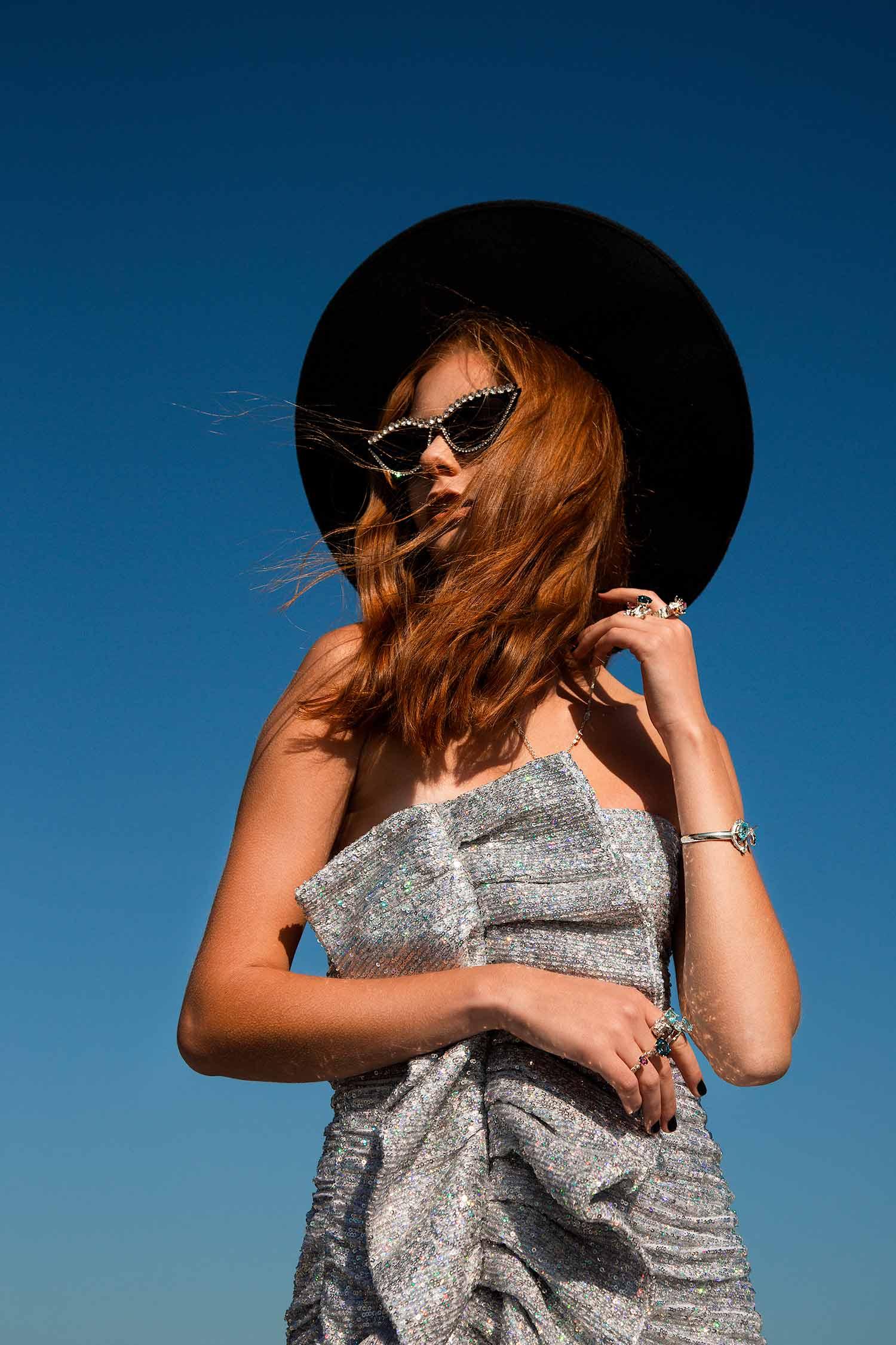 Fashion model in the blue sky, wearing Zydrune Celestial gemstone jewellery.