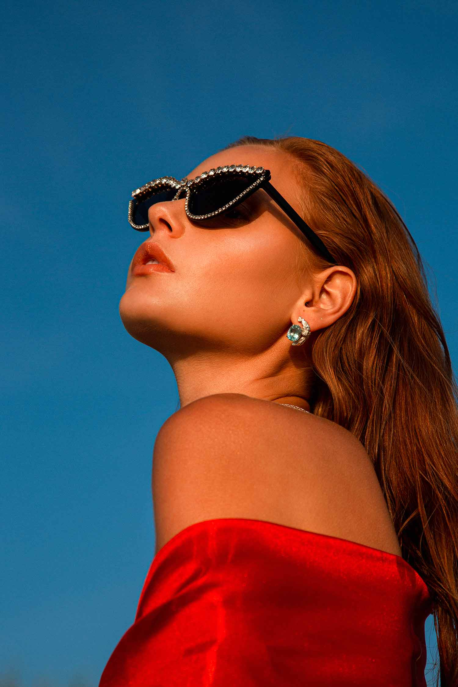 Model in the blue-sky background, wearing Zydrune Topaz earrings and black diamante sunglasses.