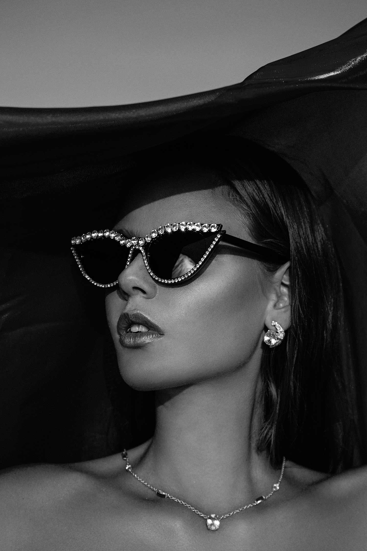 Black and white image of model wearing Zydrune Topaz earrings and elegant gemstone necklace.