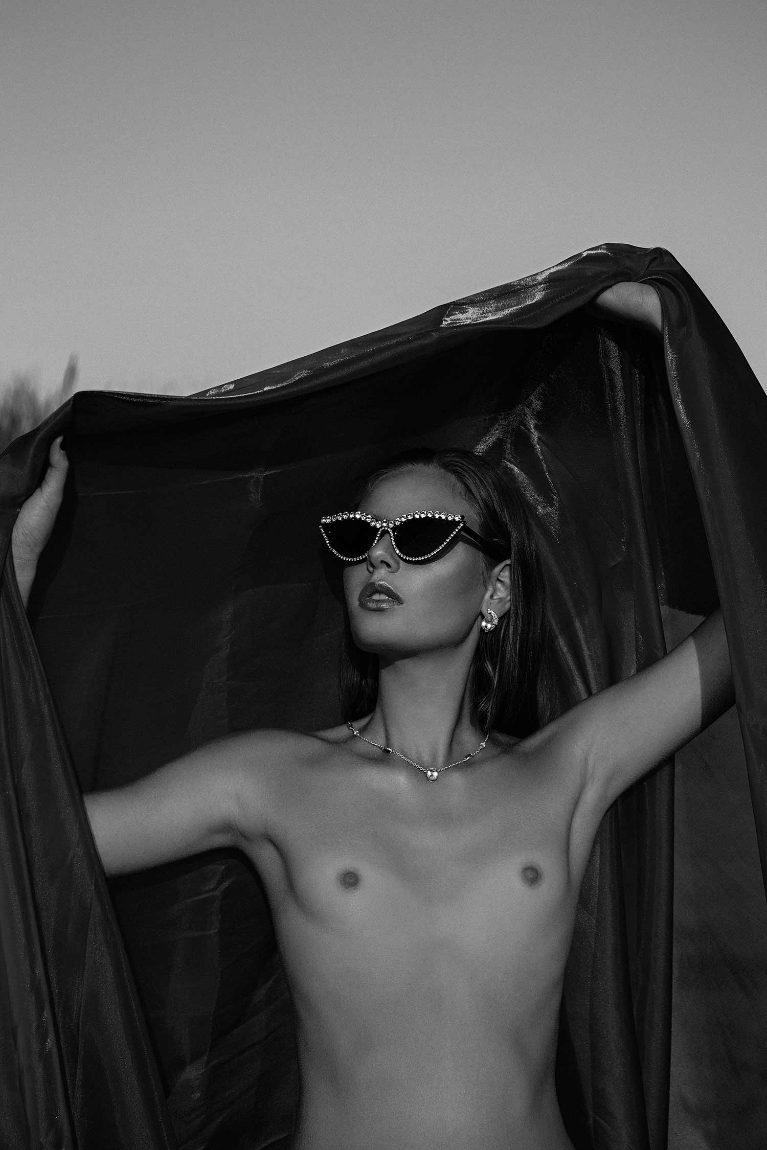 Black and white image of model wearing Zydrune necklace and earrings from Celestial collection.